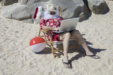Babbo Natale al lavoro dalla spiaggia